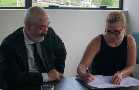 La representante de Maschwitz Mall firma el convenio ante la mirada de José Manuel Achaval.