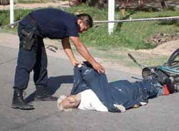 Un policía cubre el cuerpo del occiso. Atrás, su bicicleta.