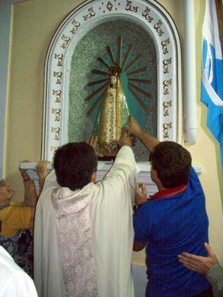 El párroco Bevilacqua entroniza la virgen en la estación de Escobar.