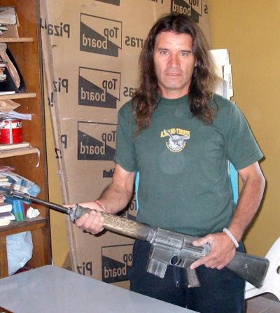 Un veterano de guerra sostiene el fusil recuperado.