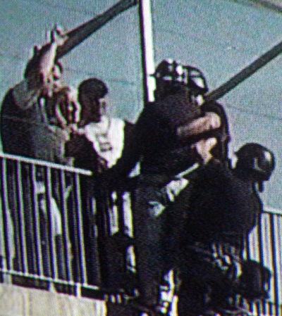 Personal del Grupo Halcón toma al joven para hacerlo descender por una escalera de rescate.