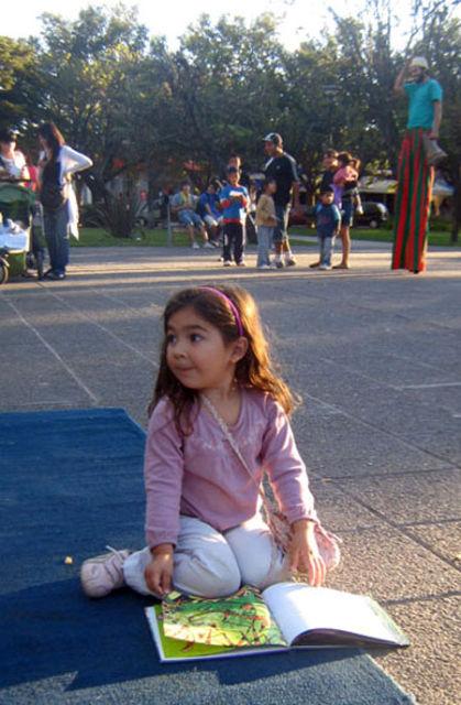 Una nena lee en plena plaza. Atrás, más chicos y un personaje en zancos.