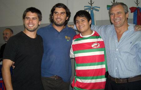 Un alumno con la remera del club, junto a jugadores y el vicepresidente de Delta Rugby Club.