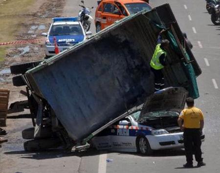 El acoplado cayó sobre el patrullero y aplastó al conductor.