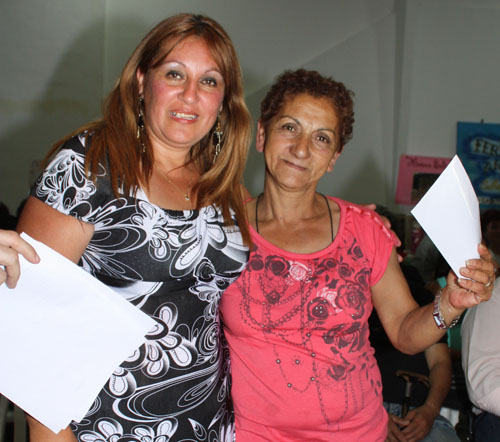 Dos microemprendedoras acaban de recibir el documento del crédito.