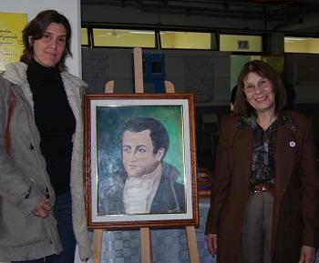 La inspectora Yacuzzi y la directora Sanz, junto al retrato de Mariano Moreno realizado por una artista local.
